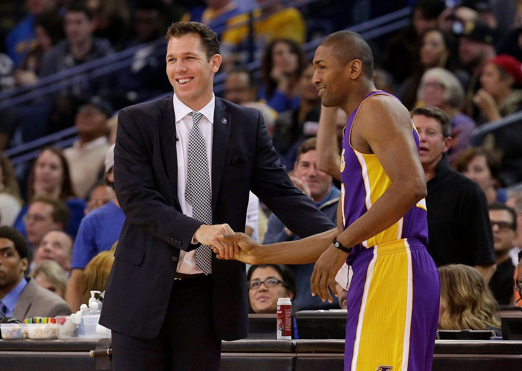 Golden State Warriors interim head coach Luke Walton, left, shakes hands with Los Angeles Lakers forward Metta World Peace during an NBA basketball game in Oakland, Calif., Tuesday, Nov. 24, 2015. (AP Photo/Jeff Chiu)